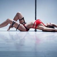 Young slim sexy pole dance woman in red lingerie